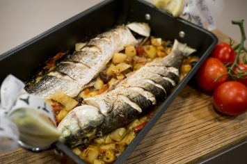 דג שלם צלוי עם תפוחי אדמה, שומר, זיתים ועגבניות