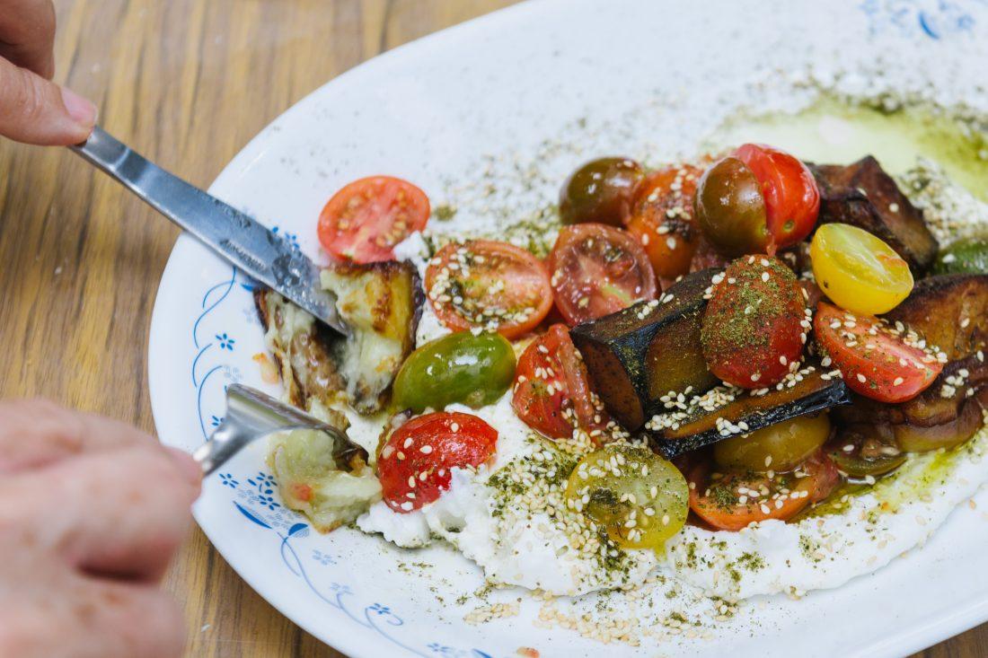 חצילים מטוגנים מוגשים על גבינת לבנה, זעתר ועגבניות שרי בצבעים