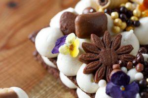 מקשטים את העוגה: מפזרים על העוגה עוגיות שאפינו, קליק, פרחים קטנים, כדורי שוקולד וממתקים. צילום: שניר גואטה