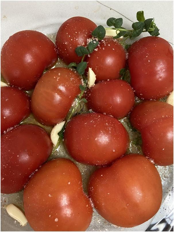 חוצים את העגבניות ל2 חצאים מזלפים שמן זית על תבנית. צילום: אופירה מור