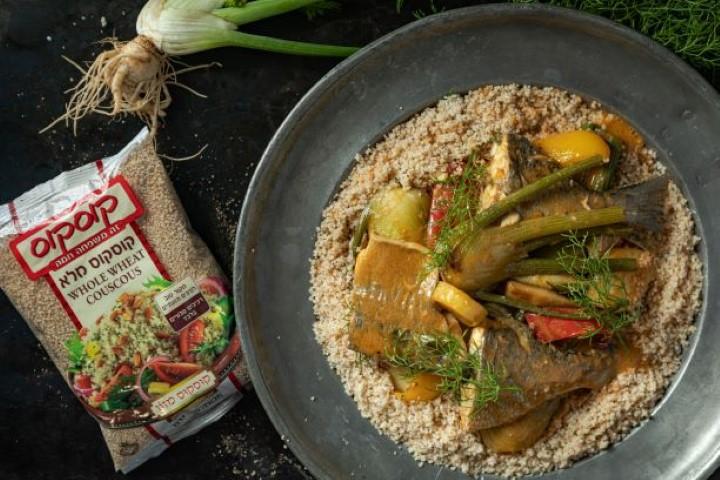 מגישים את תבשיל הדגים על קוסקוס מלא. צילום: שניר גואטה