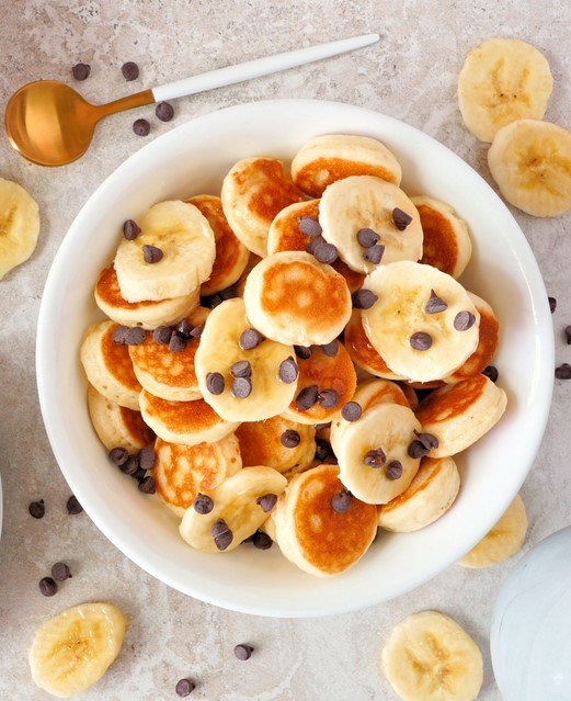 פורסים את הבננות ומוסיפים לקערה עם הפנקייקים, מפזרים את השוקולד ומסיימים בזילוף מייפל מעל. צילום: יעל רזינובסקי