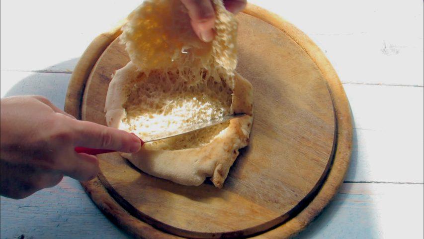 בעזרת סכין חדה חותכים עיגול גדול בצד העליון של הפיתה. צילום: Berko Made