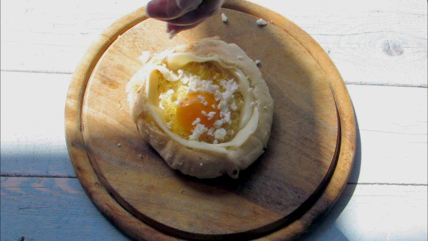פותחים בזהירות ביצה במרכז הפיתה ומפזרים גבינה בולגרית. צילום: Berko Made