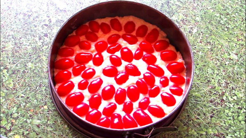 יוצקים את העיסה על בסיס הבצק ומסדרים חצאי עגבניות שרי מעל המלית, כשהצד העגול פונה כלפי מעלה. צילום: Berko Made