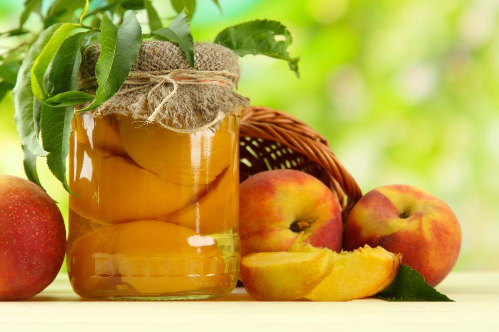 מכניסים את חצאי האפרסקים לצנצנות מעוקרות וממלאים במי הסוכר