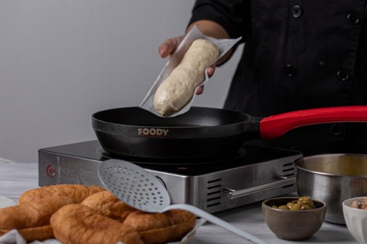 מניחים את הפריקסה עם נייר האפייה (כשנייר אפייה פונה כלפי מעלה) בשמן החם. צילום: טל סיון-ציפורין
