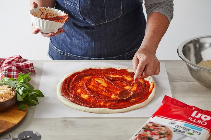 יוצקים את הרוטב במרכז הפיצה ומורחים בעזרת כף. צילום: שני הלוי