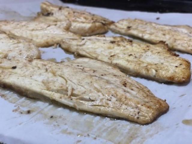 מוציאים את הדגים מהמחבת ומניחים על נייר אפייה בתבנית. צילום: פלג בכור