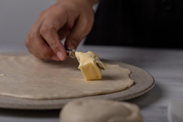 מרדדים כל כדור בצק ומורחים חמאה. צילום: טל סיון-ציפורין