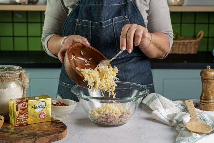 מוסיפים גבינה צהובה לקערה. צילום: שי אפגין