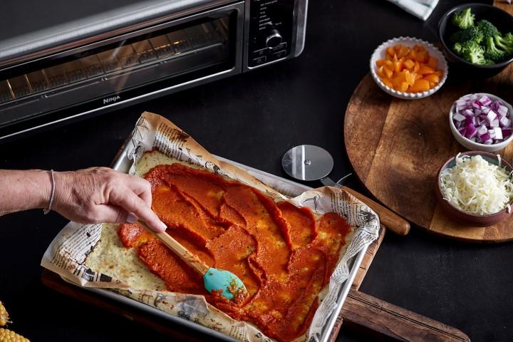 מורחים על תחתית הפיצה את הרוטב. צילום: אפיק גבאי