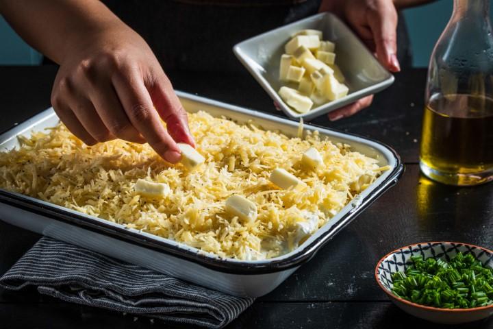 מפזרים קוביות חמאה ועוד גבינה צהובה ומכניסים לתנור. צילום: נמרוד סונדרס