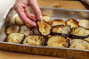 שכבת חצילים על שכבת תפוחי אדמה בתבנית.