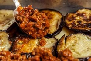 פיזור בשר על חצילים ותפוחי אדמה.